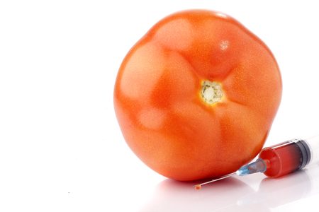 Big red tomato with and a syringe next to it. Concept for GMO.