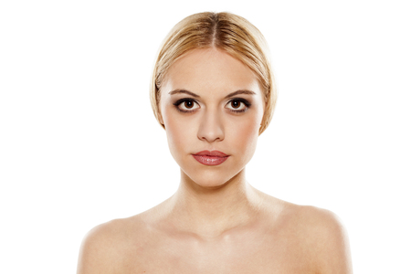 half naked: portrait of a young serious woman on a white background