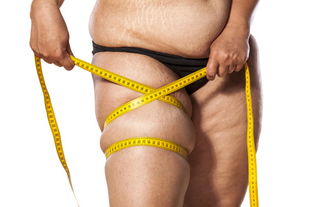 Very fat woman measuring her thighs with measuring tape on a white background Stock Photo