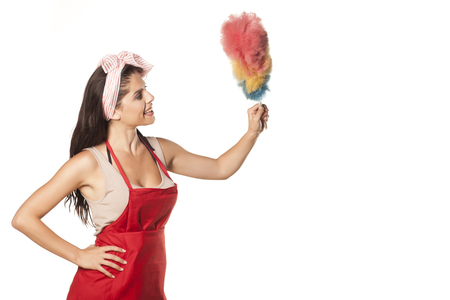 smiling and happy pretty housewife with an apron holding a duster Stock Photo