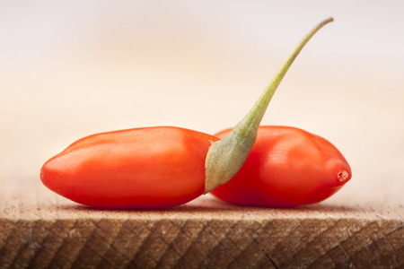 chinese wolfberry: fresh grains of goji berry on a wooden board Stock Photo
