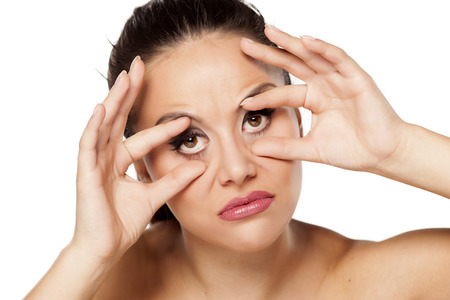 eyes open: Funny young woman holding her eyes open with her fingers
