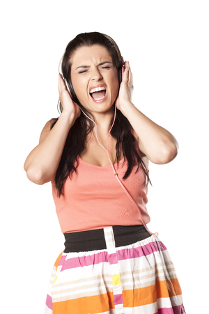 girl making painful grimace due to high volume of the music Stock Photo