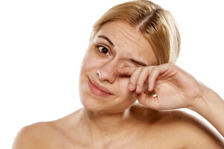 Beautiful young woman rubbing her eye with her finger