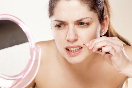 plucking: Woman removing hair above her mouth using tweezers