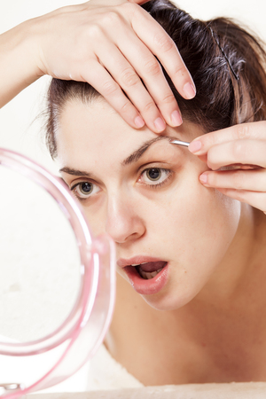 pinzas: Mujer eliminar el vello de las cejas utilizando pinzas Foto de archivo