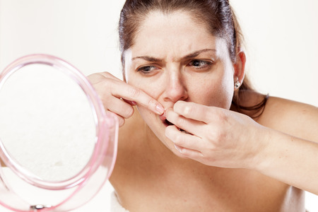 zit: Young woman squeezing her acne in front of a mirror