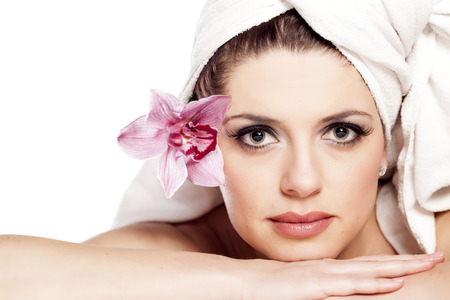 Beautiful woman with a towel on her head posing with an orchid Stock Photo