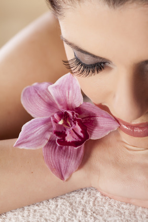 Beautiful woman with closed eyes posing with an orchid Stock Photo