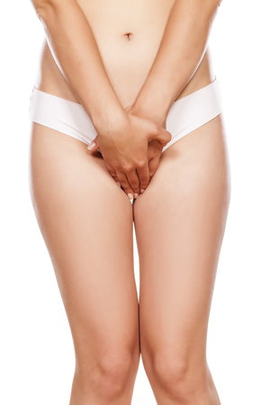 Woman in panties holding her crotch on a white background