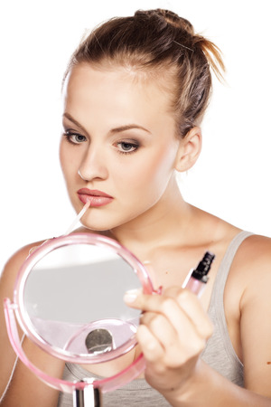 gloss: Young blonde applying lip gloss in front of a mirror