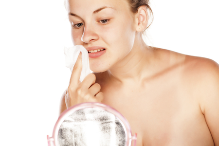 Young blonde removing her makeup with wet handkerchief in front of a mirror