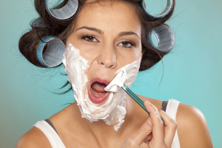Attractive young woman with curlers shaving her face Stock Photo