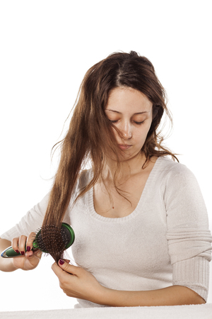 struggles: young woman struggles to comb her disheveled hair