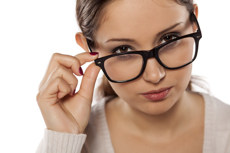 bitchy: suspicious and beautiful woman posing with eyeglasses on a white background