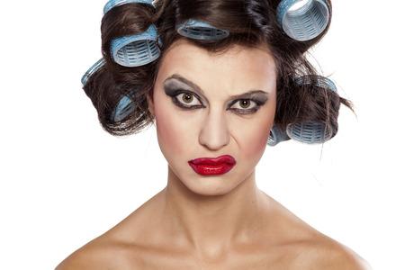 Grappig meisje met krulspelden en slechte make-up met twijfelachtige gebaar