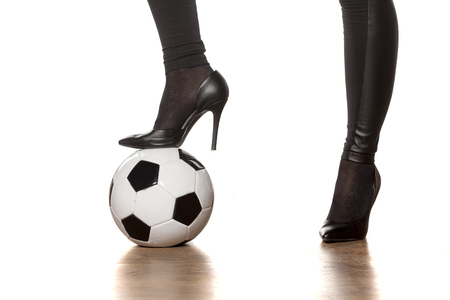 womans legs in high heels and soccer ball Stock Photo