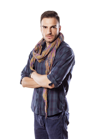 Handsome serious young man with a scarf around his neck and crossed arms Stock Photo