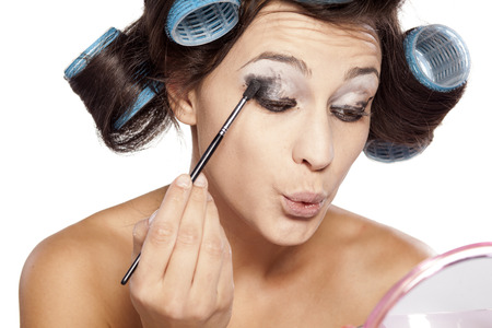 woman shadow: Woman with curlers applying eye shadow on a white background