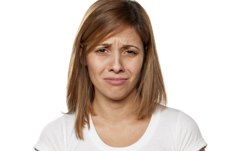 weeping beautiful young woman without make-up on a white background Stock Photo
