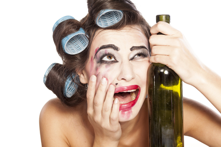 smeared mascara: Young drunk woman with curlers crying next to a bottle of wine