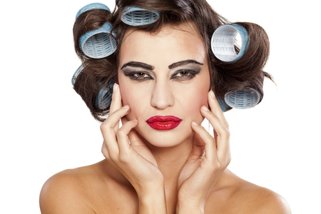 Funny woman with curlers and bad makeup on a white background Stok Fotoğraf