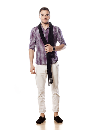 Handsome young man with a scarf around his neck standing on a white background Stock Photo