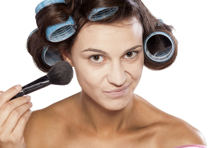 applying makeup: Smiling woman with curlers applying makeup with a brush