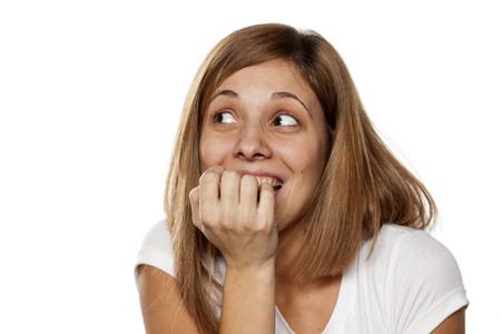 mujer joven sin maquillaje mordisqueando sus uñas