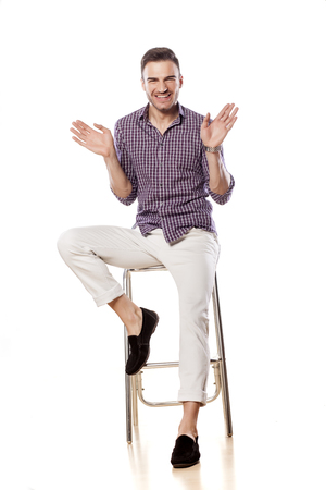 bar stool: Happy handsome gay sitting on a bar stool and waving hands Stock Photo
