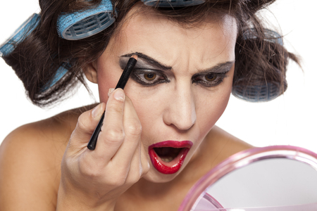 Crazy woman with curlers and bad makeup on a white background