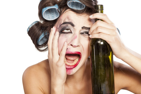 Young drunk woman with curlers crying next to a bottle of wine