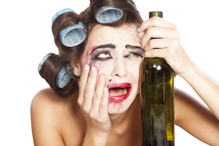 smeared: Young drunk woman with curlers crying next to a bottle of wine