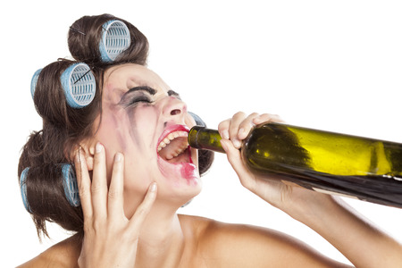 Crying drunk young woman with curlers drinking wine from a bottle
