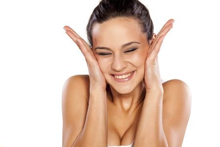 avergonzado: Avergonzado y mujer joven sosteniendo su cara con las manos sobre fondo blanco sonriente