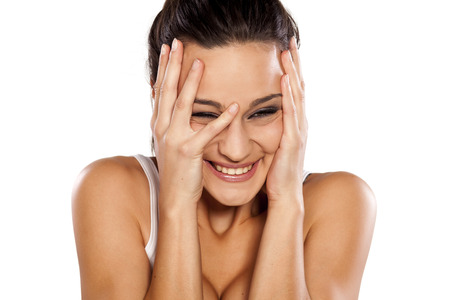 avergonzado: Ashamed and smiling young woman holding her face with her hands on white background Foto de archivo