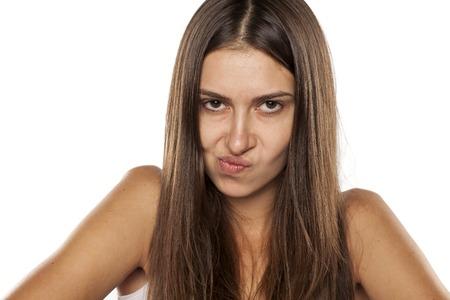 desconfianza: joven mujer enojada que mira con desconfianza a la cámara
