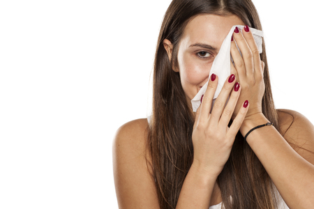 smiling young woman peeking behind a wet wipe while removing her makeup