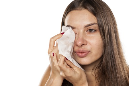 young beautiful woman removes her makeup with wet tissue Stock Photo