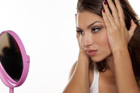 young woman tighten her face with her hands in front of the mirror Stock Photo
