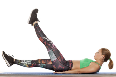 laying abs exercise: young beautiful woman doing fitness exercises for the stomach Stock Photo