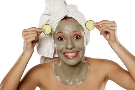 Young beautiful women posing with towel on her head, a mud mask on her face and cucumber slices Stock Photo