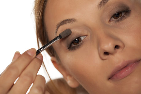 woman shadow: young beautiful woman applied eye shadow with applicator