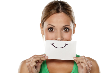 fake smile: happy young woman with emotions drawn on a piece of paper Stock Photo