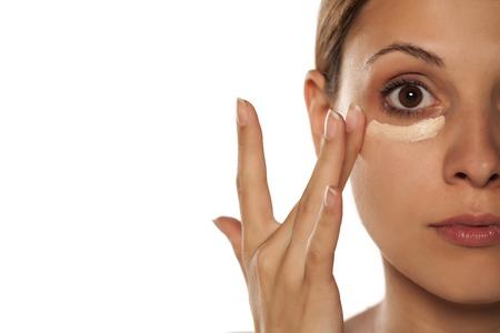 젊은 아름 다운 여자는 눈 아래에 컨실러를 적용