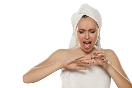 nervous young woman posing with a towel on her head with a broken fingernail