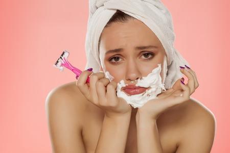 mujer joven decepcionado con espuma en la cara y una navaja en la mano Foto de archivo