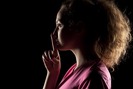 young woman with the face in the shadow holding finger on her lips Stock Photo