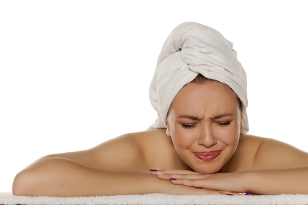 scowling young woman with a towel on her head Stock Photo