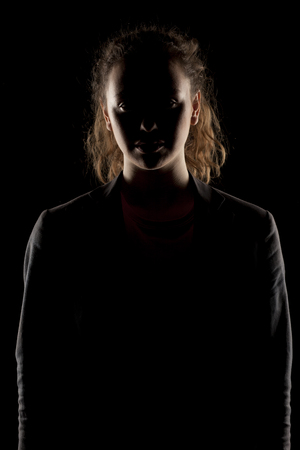 unnamed: portrait of a girl with the face in shadow on a dark background